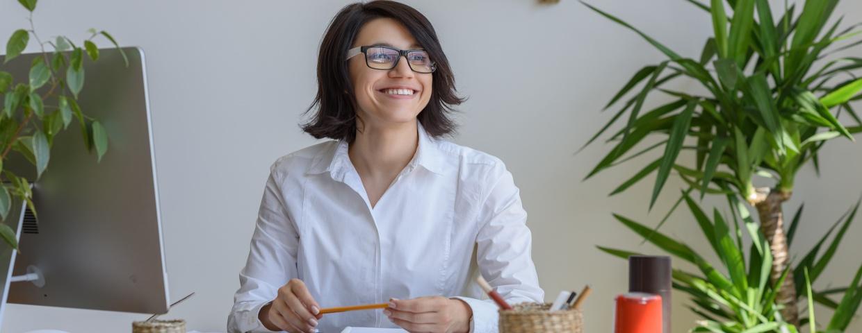 smiling businesswoman, natural lighting, plants