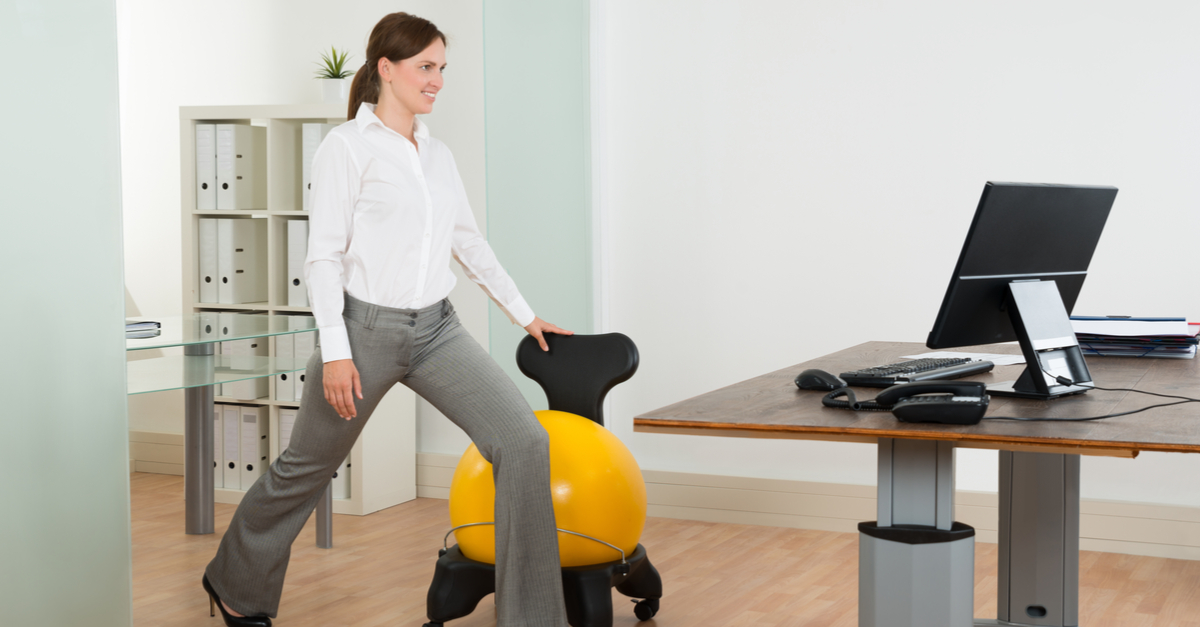 person stretching in front of standing desk